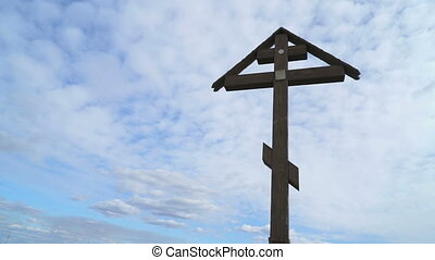 Orthodox cross on a background of floating clouds and blue...