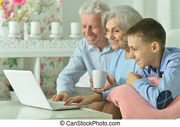 Boy with his grandparents and laptop - Portrait of a boy...