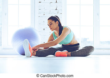 Great progress. Young beautiful woman in sportswear doing stretching while sitting on the floor in front of window at gym