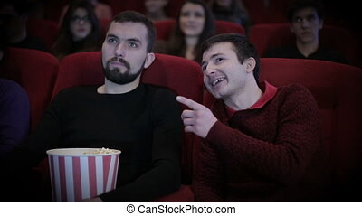 Man talks out loud with man in cinema - Young man talks out...