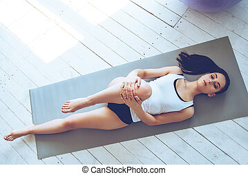 Practicing Pilates. Top view of young beautiful young woman in sportswear doing stretching while lying on exercise mat at gym