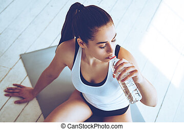 Sip of fresh water after great workout. Top view of beautiful young woman drinking water while sitting on exercise mat at gym
