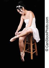 Ballerina lying her ballet slippers.