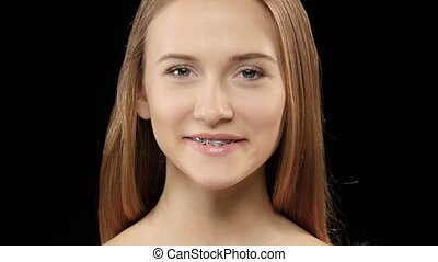 Beautiful girl with braces on her teeth white posing for the...
