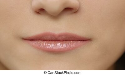 Female lips. Girl showing braces on teeth. White. Closeup -...