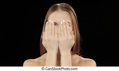 Model covers her face with her hands, and then shows his...