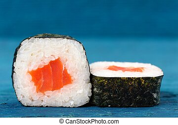 Pair of japanese rolls with salmon, rice and nori on sky...