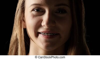 Female in the shade with braces smiling sincerely. Black -...