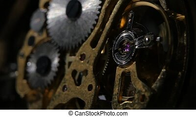 Moving metal gears inside working watch mechanism. Close up...