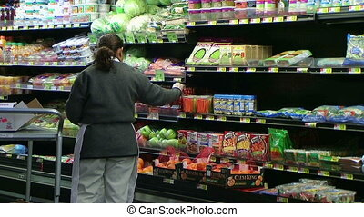 Woman Stocking Tomatoes In Produce - Woman stocking tomatoes...