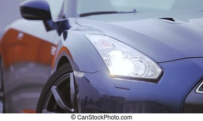 White headlights of dark blue new car stand on parking. Presentation of automobile. Cold shades
