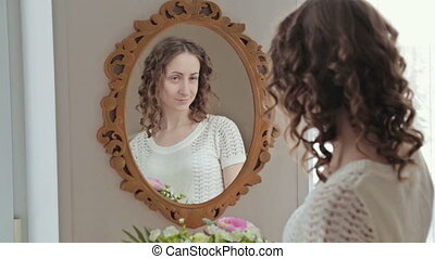 Woman combing hair near mirror - Young woman combing hair...