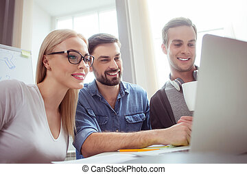 Cheerful young colleagues are working with computer -...
