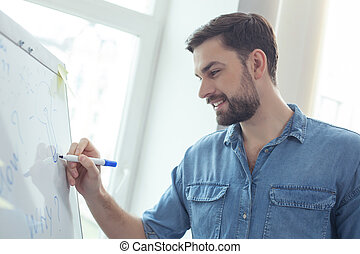 Skillful male worker is making notes - Attractive young...