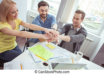 Cheerful three office workers made a deal - We are a great...