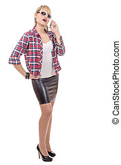 young woman clothed in a leather skirt and shirt, on phone -...