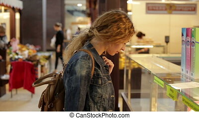 Young woman chooses the goods in big shop