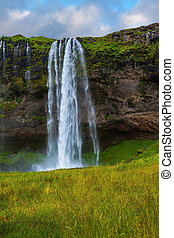 Seljalandsfoss waterfall in July Large rainbow decorates a...
