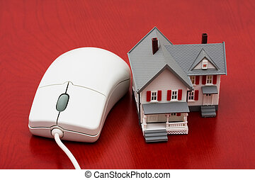 Online Real Estate - A model house sitting with a computer...