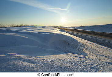 winter road , snow - a small country road passes in a field...