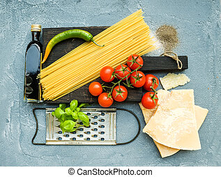 Ingredients for cooking pasta. Spaghetti, Parmesan cheese, cherry tomatoes, metal grater, olive oil and fresh basil on grey-blue concrete background