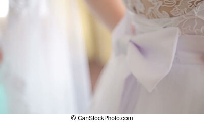 bridesmaid tying bow on wedding dress - bridesmaid tying the...