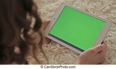 Woman at home using electronic tablet - Back view of woman...