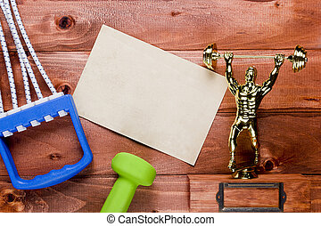 Figure weightlifter, dumbbells and expander on a wooden...