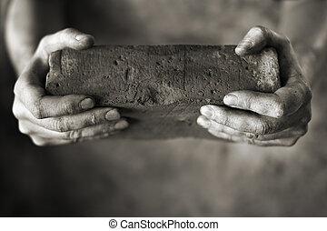 Old brick - Sepia toned photo of DIrty hands holding an old...