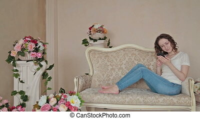 Woman using phone at home - Young woman using mobile phone...