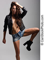 Woman body in denim jeans shorts and black leather jacket -...
