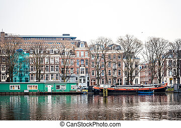 Beautiful view of Amsterdam canals with bridge and typical dutch houses.