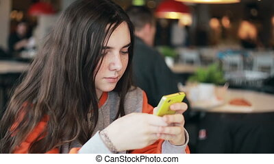 Teenage girl using smartphone in cafe.