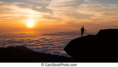 Man standing on cliff above the cloudy valley - Male...