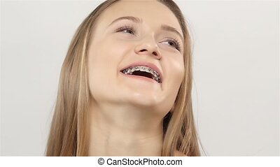 Woman laughs and shows her smile with braces. White. Slow...