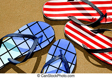flip-flops - two pairs of flip-flops floating on the sand on...