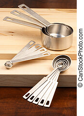 kitchen utensils over wood - set of measuring spoons and...