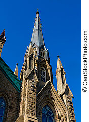 Gothic Spire into Clear Blue Sky - Old Stone Church in...
