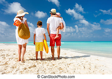 Family beach vacation - Back view of a happy family at...