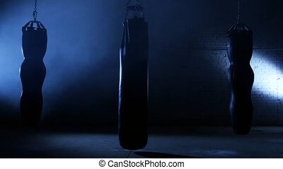 Punching bag swings in the hall, sports hall in which the...