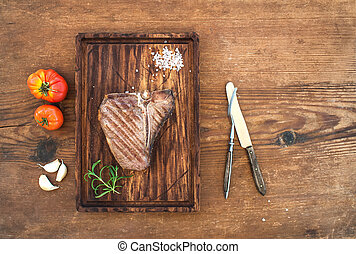Cooked meat t-bone steak on serving board with garlic...