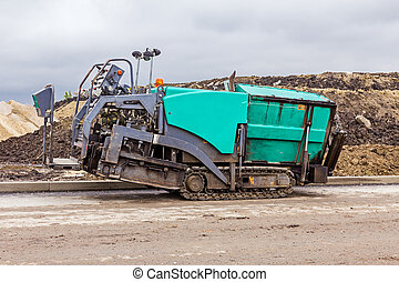 Tarmac road laying machine. Asphalt spreader. - Side view on...