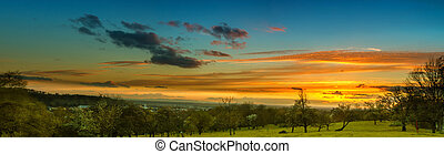 Panoramic image of colorful sunset in the countryside