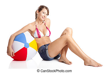 Beautiful young woman posing in bikini with a beach ball