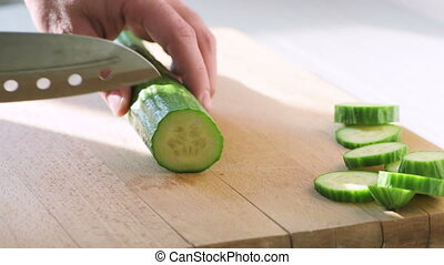 Slow motion video of slicing fresh long cucumber, on a...