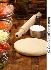pizza ingredients and utensils  on  wood cutting board