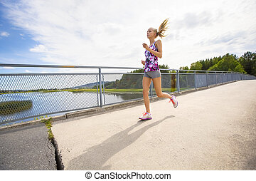 Motivated young woman running fast on bridge over a lake -...
