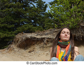 Breathing the air - Young woman relaxing on the sand