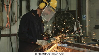 worker grinding metal using a circular metal grinder