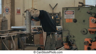 Welder welding metal parts in a workshop